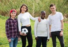 Retrato de cuatro amigos que presentan en campo del campo con la bola Imagen de archivo libre de regalías
