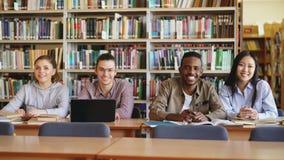 Retrato de cuatro estudiantes multi-étnicos que se sientan en el escritorio largo en biblioteca espaciosa grande con las pilas de almacen de video