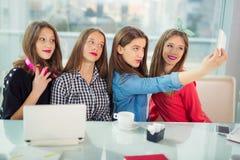 Retrato de cuatro mujeres jovenes que se sientan en la tabla en el selfie de la toma del café con el teléfono elegante Imágenes de archivo libres de regalías