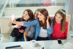 Retrato de cuatro mujeres jovenes que se sientan en la tabla en el selfie de la toma del café con el teléfono elegante Fotos de archivo