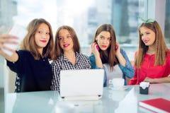 Retrato de cuatro mujeres jovenes que se sientan en la tabla en el selfie de la toma del café con el teléfono elegante Fotografía de archivo libre de regalías
