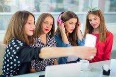 Retrato de cuatro mujeres jovenes que se sientan en la tabla en el selfie de la toma del café con el teléfono elegante Fotografía de archivo