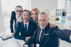 Retrato de cuatro que sonríen, hombres de negocios financieros, atractivos foto de archivo libre de regalías