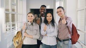 Retrato de cuatro varón positivo y estudiantes multi-étnicos que se colocan en pasillo blanco espacioso en universidad metrajes