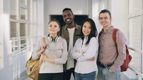Retrato de cuatro varón y estudiantes multi-étnicos atractivos positivos sonrientes que se colocan en pasillo blanco espacioso almacen de video