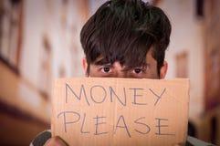 Retrato de desamparados con la descripción de la cartulina del dinero por favor, ocultando el hald de su cara, en un fondo borros Imagen de archivo