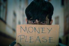 Retrato de desamparados con la descripción de la cartulina del dinero por favor, ocultando el hald de su cara, en un fondo borros Foto de archivo libre de regalías