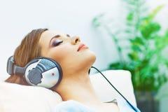 Retrato de descansar a la mujer joven en casa con música que escucha Imágenes de archivo libres de regalías