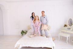 Retrato de descansos de combate da família, saltando na cama junto dentro imagem de stock