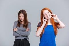 Retrato de dois alegres e de jovens mulheres infelizes imagens de stock