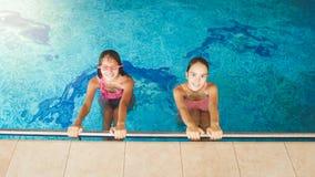 Retrato de dois amigos de adolescentes que nadam e que t?m o divertimento dentro na piscina fotos de stock