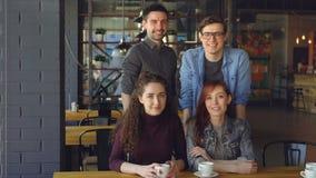 Retrato de dois amigos felizes dos jovens dos pares na roupa ocasional no café moderno com copos de chá que sorriem e que olham vídeos de arquivo