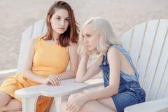 Retrato de dois amigos unformal caucasianos brancos tristes pensativos dos estudantes do moderno das moças fora no verão da praia Imagem de Stock
