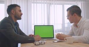 Retrato de dois homens de negócios bem sucedidos adultos que têm uma discussão formal com o portátil com a tela chave do croma ve video estoque