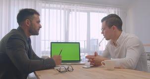 Retrato de dois homens de negócios bem sucedidos adultos que têm uma discussão formal com o portátil com a tela verde do croma no video estoque