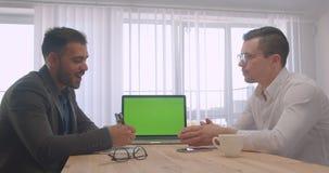 Retrato de dois homens de negócios bem sucedidos adultos que têm uma discussão formal com o portátil com a tela verde no escritór vídeos de arquivo