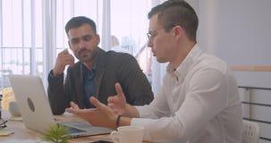 Retrato de dois homens de negócios consideráveis bem sucedidos adultos que trabalham no portátil e que têm uma discussão no escri video estoque