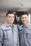 Retrato de dois mecânicos de sorriso da garagem foto de stock royalty free