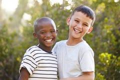 Retrato de dois meninos fora que riem e que olham à câmera imagem de stock royalty free