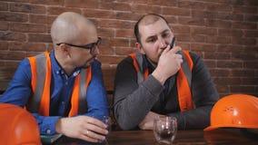 Retrato de dois trabalhadores que vestem os capacete de segurança que tomam uma ruptura do café bebendo do trabalho e que descans video estoque