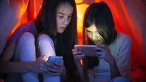 Retrato de dos adolescentes con los teléfonos elegantes debajo de la manta en la noche Fotografía de archivo
