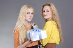 Retrato de dos adolescentes con un rectángulo de regalo Imagen de archivo libre de regalías