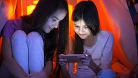 Retrato de dos adolescentes en pijamas que hojean Internet en el teléfono móvil en la noche Fotos de archivo libres de regalías