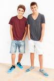 Retrato de dos adolescentes hispánicos que se inclinan contra la pared Imagenes de archivo