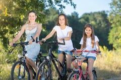 Retrato de dos adolescentes que montan las bicicletas con la madre en parque Imagen de archivo