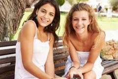 Retrato de dos adolescentes que se sientan en banco de parque junto Fotografía de archivo