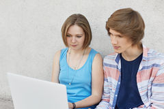 Retrato de dos adolescentes que sientan junto mirar seriamente el ordenador portátil que lee el libro en línea Adolescente de mod Fotos de archivo libres de regalías