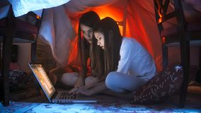 Retrato de dos adolescentes que usan el ordenador portátil en el ngiht antes de irse a la cama Fotos de archivo