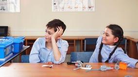 Retrato de dos alumnos que se sientan por un escritorio metrajes