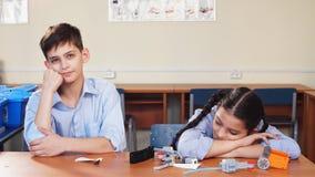 Retrato de dos alumnos que se sientan por un escritorio almacen de metraje de vídeo