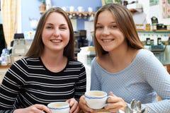 Retrato de dos amigos adolescentes femeninos que se encuentran en café Fotografía de archivo libre de regalías