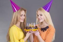 Retrato de dos amigos con la torta de cumpleaños Imagen de archivo