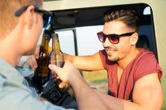 Retrato de dos amigos que tuestan con las botellas de cerveza en coche Imagen de archivo