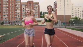 Retrato de dos atletas jovenes que compiten en la raza en el estadio por la mañana, verano, al aire libre metrajes