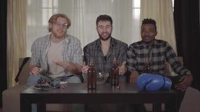 Retrato de dos cauc?sicos y de los hombres afroamericanos uno que descansan junto en casa, boxeo de observaci?n en la TV Botellas almacen de metraje de vídeo