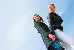 Retrato de dos chicas jóvenes sobre el cielo imagenes de archivo
