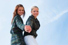 Retrato de dos chicas jóvenes sobre el cielo fotografía de archivo libre de regalías