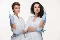 Retrato de dos cirujanos de las mujeres que muestran las jeringuillas fotografía de archivo libre de regalías