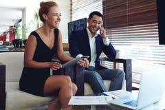 Retrato de dos empresarios alegres sonrientes que se preparan para encontrarse, mujer joven que usa la almohadilla táctil Imagen de archivo libre de regalías