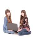 Retrato de dos hermanas de los gemelos con el ordenador portátil Imágenes de archivo libres de regalías
