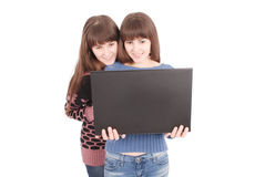 Retrato de dos hermanas de los gemelos con el ordenador portátil Fotografía de archivo libre de regalías