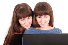 Retrato de dos hermanas de los gemelos con el ordenador portátil Imagenes de archivo