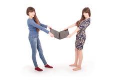 Retrato de dos hermanas de los gemelos con el ordenador portátil Imagen de archivo