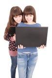 Retrato de dos hermanas de los gemelos con el ordenador portátil Fotografía de archivo