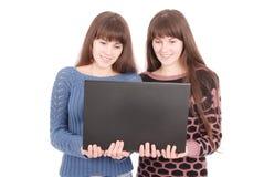 Retrato de dos hermanas de los gemelos con el ordenador portátil Imagen de archivo libre de regalías