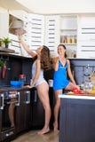 Retrato de dos hermanas gemelas que se divierten en la mañana que prepara el desayuno Fotos de archivo